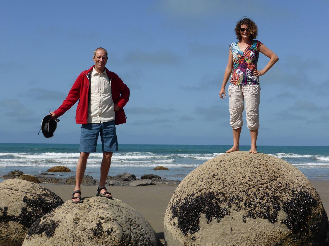 Gekke mensen boven op gekke ronde bolders op het strand